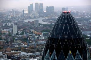 """The Swiss Re Insurance building, also known as """"the Gherkin"""", foreground, and the towers of the Canary Wharf business district are seen against the city skyline in London, U.K. on Thursday, July 12, 2012. Banks being probed for attempting to rig benchmark interest rates could face $6 billion of related litigation costs, analysts at Morgan Stanley estimated. Photographer: Jason Alden/Bloomberg via Getty Images"""